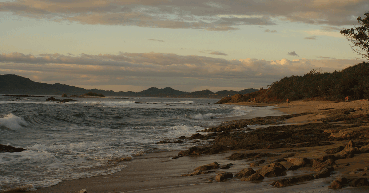 Sun sets across Playa Tamarindo as the waves crash against the shore