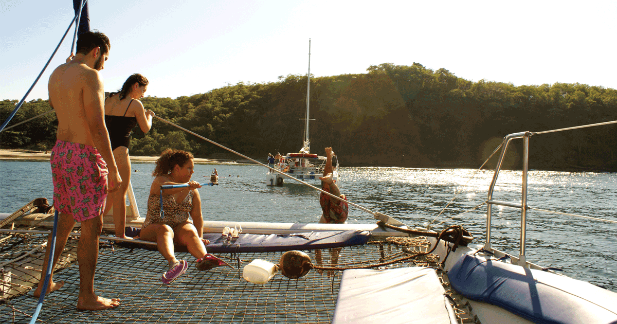 Group of friends jumping off catamaran in Tamarindo